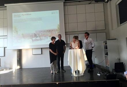 Til venstre borgmester Benedikte Kjær, der ser til mens kommunaldirektør Stine Johansen skriver under på kontrakten med Kjær & Richter i en sal på Skolen i Bymidten.